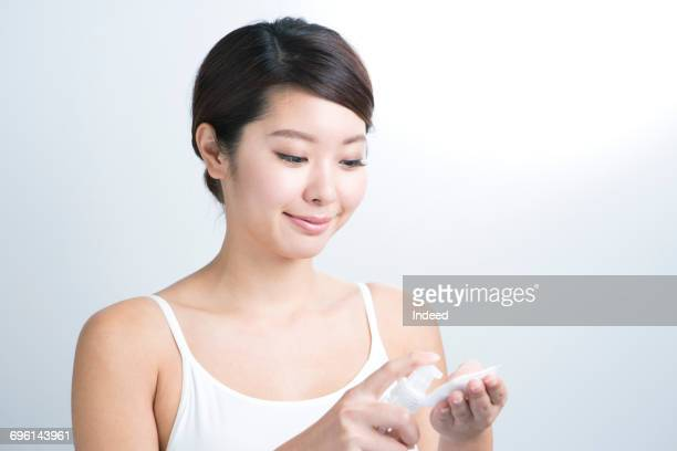 Young woman applying lotion on cotton pad