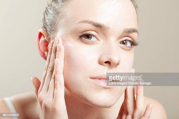 young woman applying lotion on face, close-up - cheek stock pictures, royalty-free photos & images