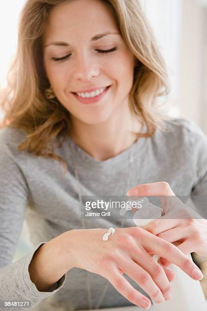 Young woman applying lotion on her hands
