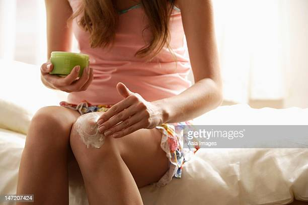 young woman applying lotion to knee - legs and short skirt sitting down stock pictures, royalty-free photos & images