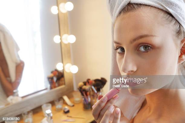 Young woman applying makeup after shower