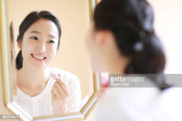 young woman applying make-up in mirror - 鏡 ストックフォトと画像