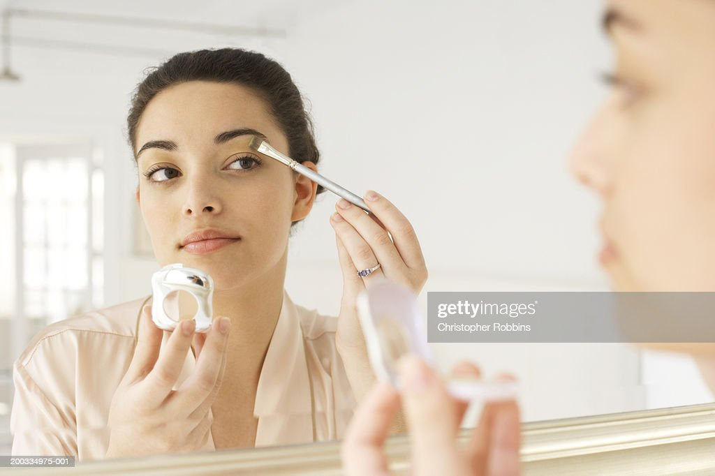 Young woman applying make-up in mirror, using brush, close-up : Stock Photo