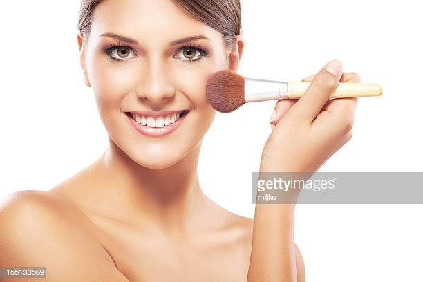 Young woman applying makeup on face