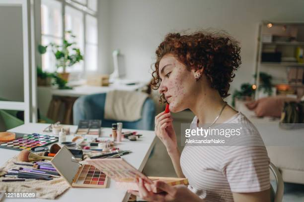 young woman applying make-up - acne stock pictures, royalty-free photos & images