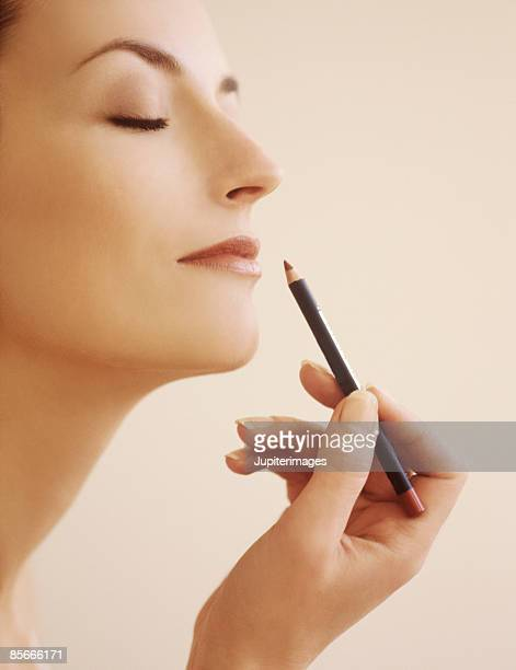 young woman applying makeup - lip liner stock photos and pictures