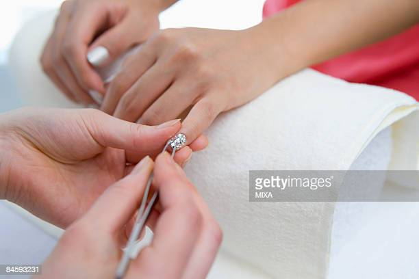 Young woman applying manicure at nail salon