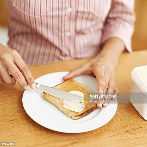 young woman applying margarine to a slice of toast - margarine stock pictures, royalty-free photos & images