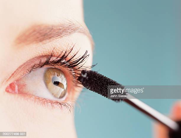 Young woman applying mascara, close-up of eye