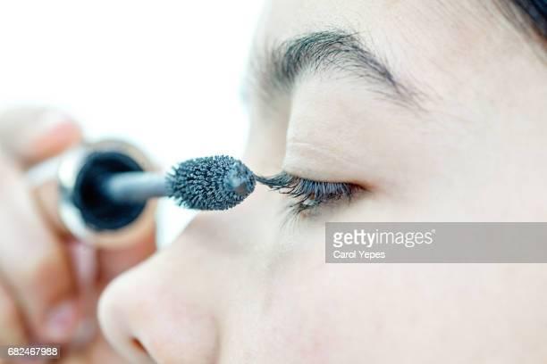 Young woman applying mascara, close-up of eye