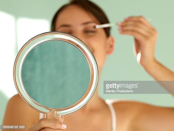 Young woman applying mascara, holding hand mirror, (focus on foreground)