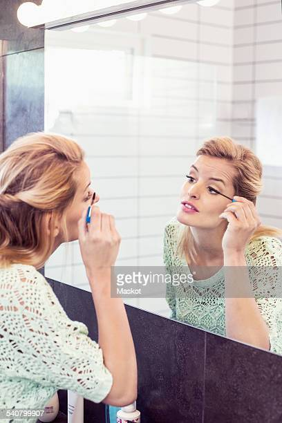 Young woman applying mascara in front of bathroom mirror