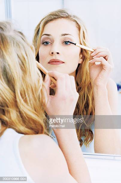 Young woman applying mascara in mirror (focus on reflection)