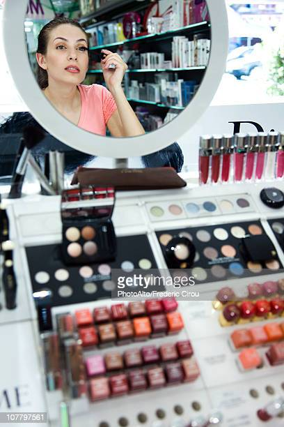 Young woman applying mascara in store