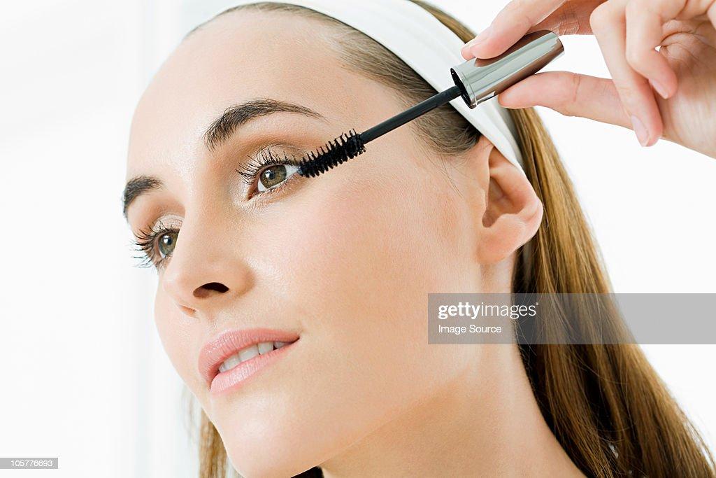 Young woman applying mascara : Stock Photo