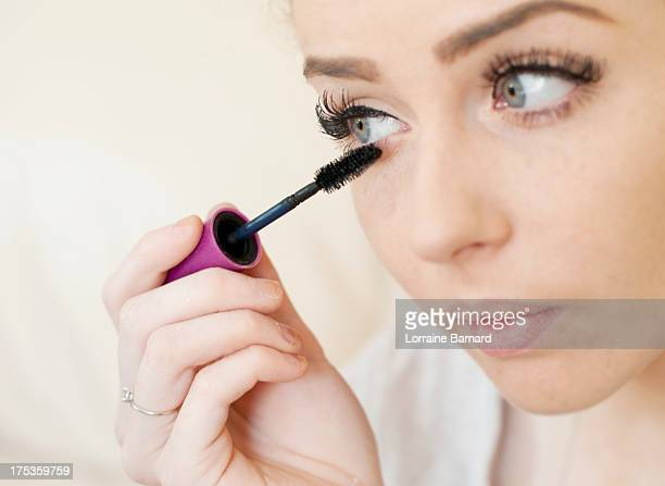young woman applying mascara - mascara stock pictures, royalty-free photos & images