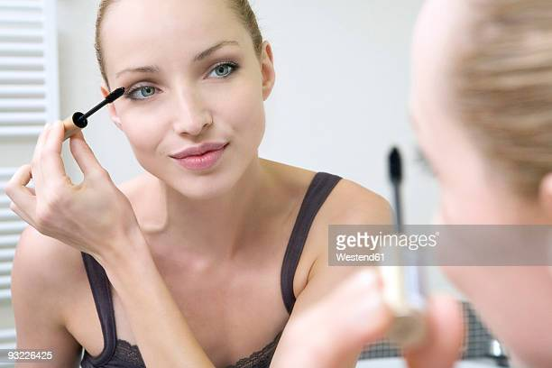 Young woman applying mascara, portrait, close-up
