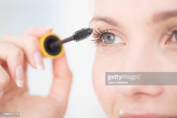 young woman applying mascara to eyelashes, close-up - mascara photos et images de collection