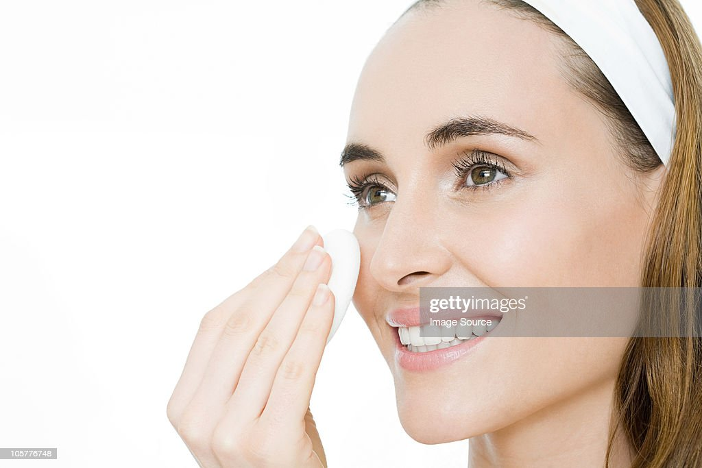 Young woman applying moisturiser : Stock Photo