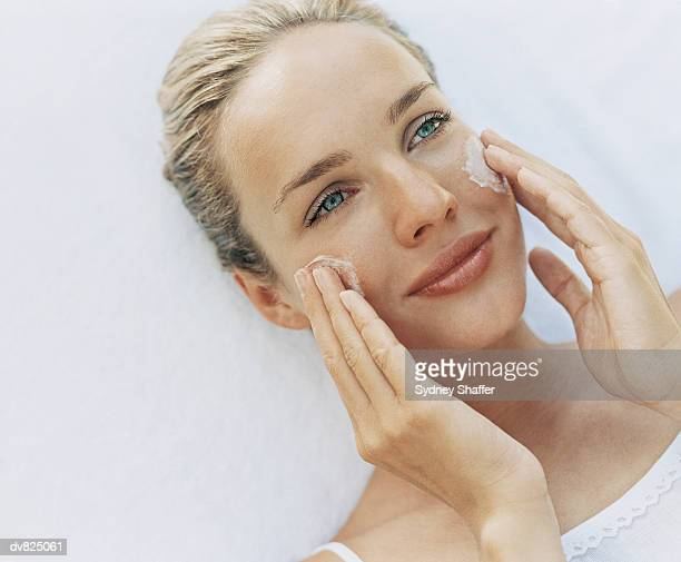 Young Woman Applying Moisturiser to Her Cheeks
