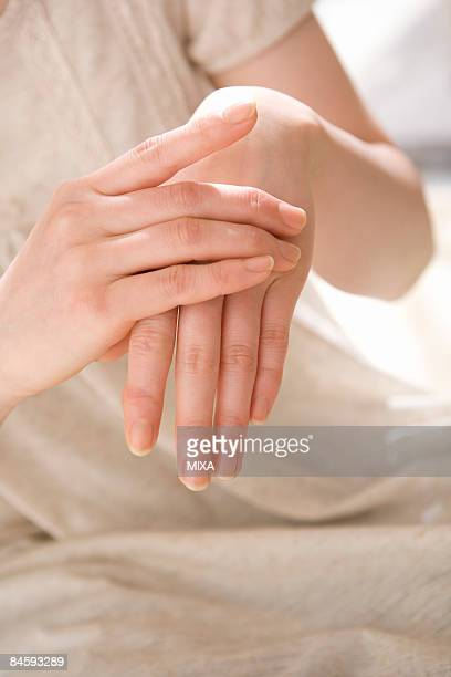 young woman applying moisturizer - hand cream stock photos and pictures