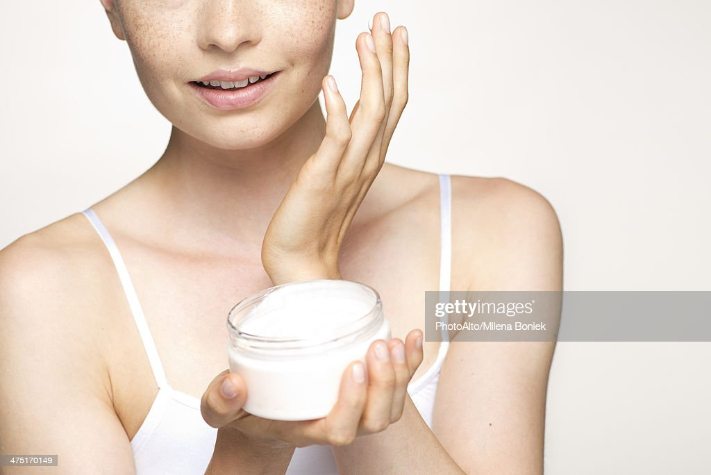 Young woman applying moisturizer to face, portrait : Stock Photo