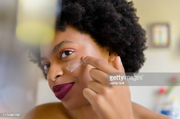 young woman applying moisturizer to her face - 頬 ストックフォトと画像