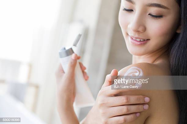 Young woman applying moisturizer to shoulder