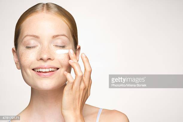 young woman applying mositurizer under eye - aspecto da epiderme - fotografias e filmes do acervo