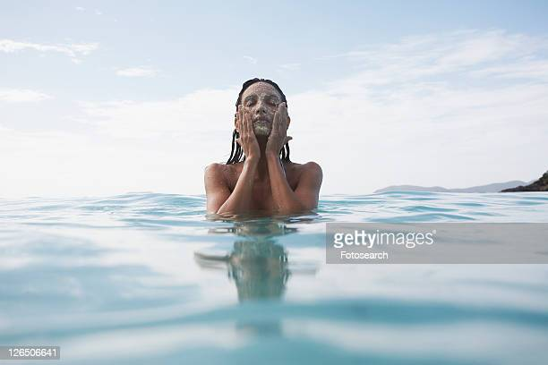 Young woman applying mud mask in water