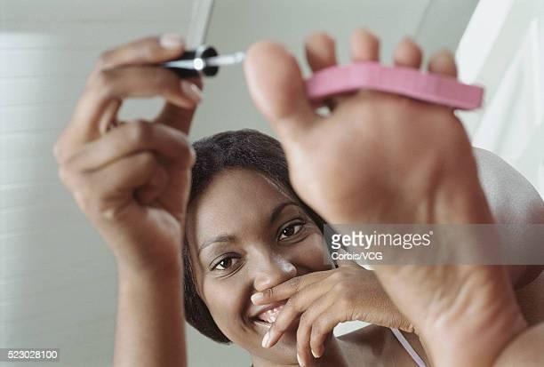 young woman applying nail polish to her toenails - black pedicure fotografías e imágenes de stock