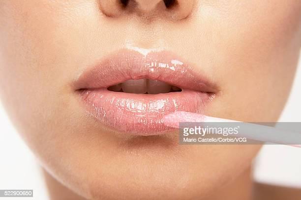 Young woman applying pink lipgloss