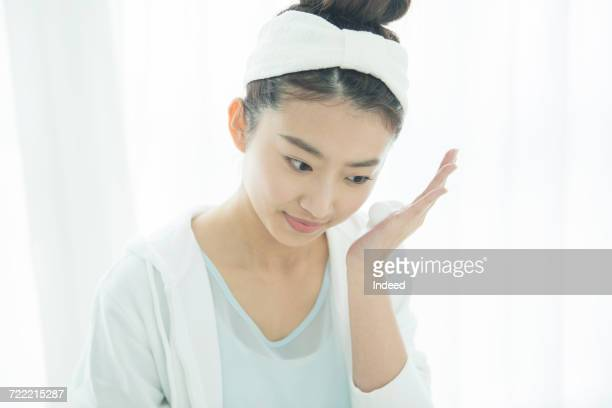Young woman applying soap suds to cheek