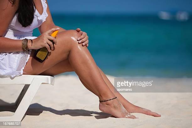 jovem mulher aplicando um protector solar na perna na praia - melanoma imagens e fotografias de stock