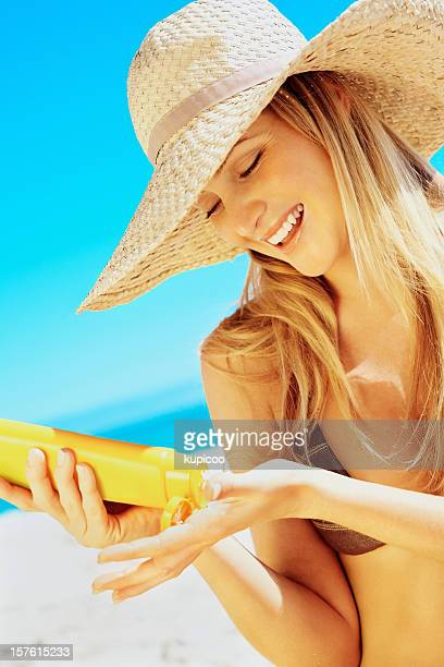 Young woman applying suntan lotion on a beach