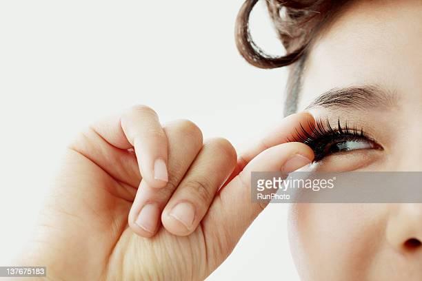 young woman applying the false eyelash - false eyelash stock pictures, royalty-free photos & images