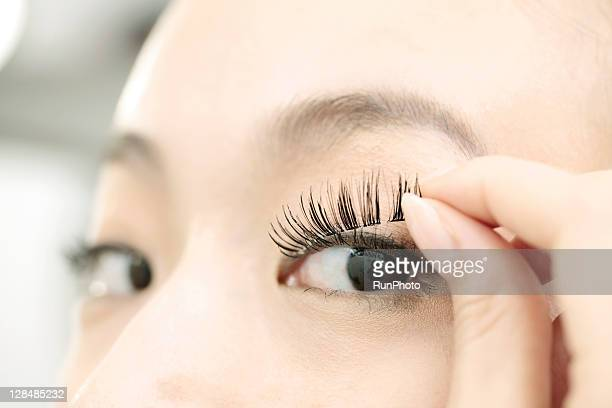 young woman applying the false eyelashes - false eyelash stock pictures, royalty-free photos & images