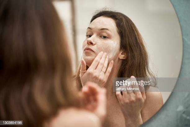young woman applying wash foam to her face. - clean stock pictures, royalty-free photos & images