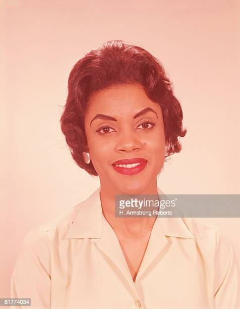young woman arching eyebrows, smiling, portrait. (photo by h. armstrong roberts/retrofile/getty images) - black blouse stock pictures, royalty-free photos & images