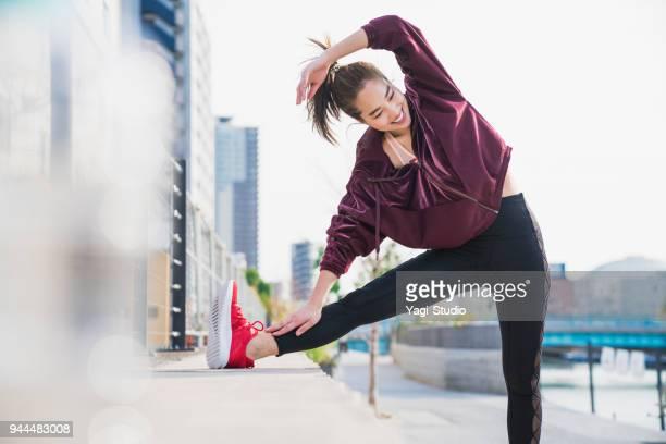 若い女性が屋外ストレッチします。 - スポーツウェア ストックフォトと画像