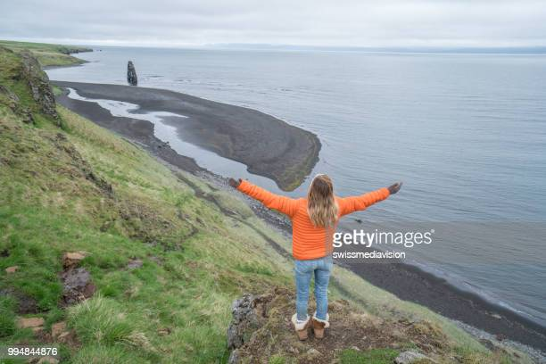 Young woman arms outstretched at Hvitserkur basalt stack along the eastern shore of the Vatnsnes peninsula, in northwest Iceland
