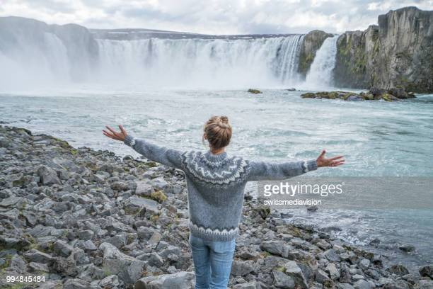 Young woman arms outstretched at spectacular waterfall in Iceland
