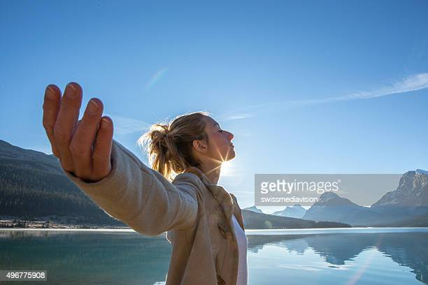 Young woman arms outstretched by the lake, sun rising