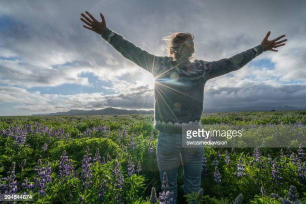 Young woman arms outstretched in flower field for freedom at sunset Springtime