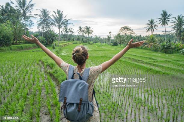 Young woman arms outstretched in rice terrace, Ubud- Bali