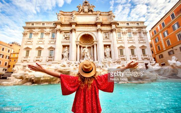 young woman arms raised at trevi fountain rome - trevi fountain stock pictures, royalty-free photos & images