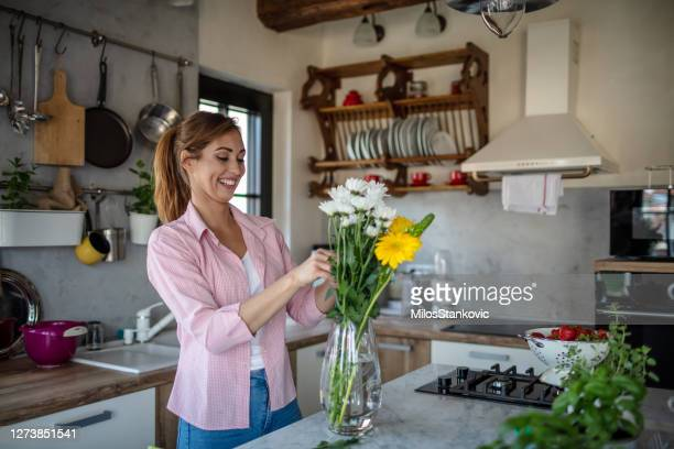 young woman arranging a flowers in vases at home. - arranging stock pictures, royalty-free photos & images