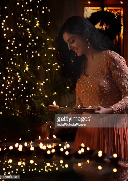 young woman arranging oil lamps at a diwali festival - diya oil lamp stock pictures, royalty-free photos & images