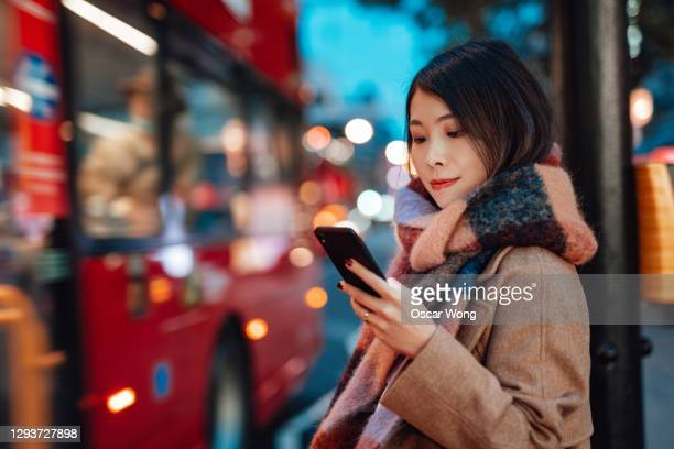 young woman arranging taxi service with smartphone on the city street at night - transportation stock pictures, royalty-free photos & images
