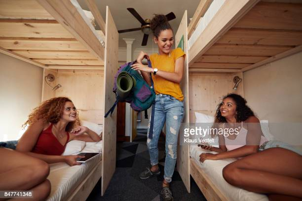Young woman arriving at hostel room, two other women laying in bunk beds
